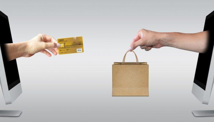 Illustration d'un achat en ligne : une main tend une carte bancaire, l'autre tend un sachet